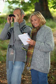 Senior woman and senior man watching through binoculars — Stock Photo