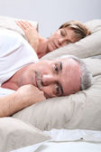 Um homem está acordado quando a esposa está dormindo — Foto Stock