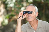 Man using a pair of binoculars — Stock Photo