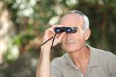 Man using a pair of binoculars — Stock Photo