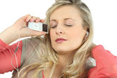 Blonde with eyes shut listening to music — Stock Photo
