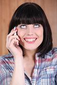Kobieta z szerokim uśmiechem, rozmawia przez telefon — Zdjęcie stockowe