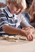Young boy playing dominoes with his father — Stock Photo