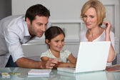 Young girl using a laptop computer with her parents — Stock Photo