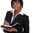 Afro-American businesswoman writing in her agenda — Stock Photo