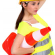 A traffic controller carrying a pylon - Stock Photo