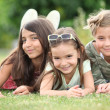 Three young girls lying on the grass — Stock Photo