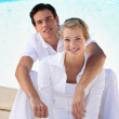 Portrait of a young couple sitting at the poolside — Stock Photo
