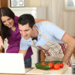 Couple following a recipe on a laptop - Stockfoto