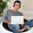 Smiling man with laptop and headset — Stock Photo