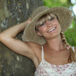 Summery woman standing by a tree — Foto de Stock