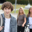 Young man standing in front of two girls with bikes — Stock Photo