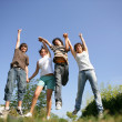 Group of teenagers holding hands and jumping in the air — Stock Photo #8654422