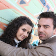 Attractive couple stood in front of graffiti-ed wall — Stock Photo #8655089