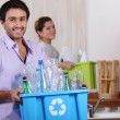 Stock Photo: Young couple recycling plastic in their kitchen