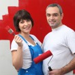Couple painting a room red - Stok fotoğraf