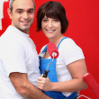 Couple painting a room bright red - Stock Photo