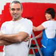 Couple repainting home walls in red - Stock Photo