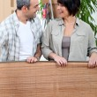 Stock Photo: Couple unrolling mat in their new home