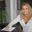 Young blond woman writing on clipboard — Stock Photo #8655404
