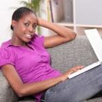ラップトップ コンピューターとソファーに横たわって若い女性 — ストック写真 #8655760
