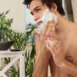 Young man applying shaving cream — Stock Photo
