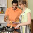 Stock Photo: Couple preparing meal together in their kitchen