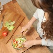 Stock Photo: Girl preparing salad on countertop