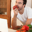 Man biting into an apple - Stock Photo