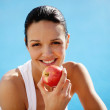 Cheerful woman eating an apple — Stock Photo