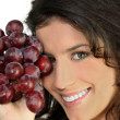 Woman with bunch of ripe grapes — Stock Photo