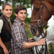 Young couple stood by horses — Stock Photo
