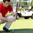 Golfer crouched next to the hole - Photo