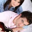 A young couple on bed, the man is playing guitar - Stockfoto