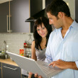 Couple stood in kitchen with laptop — Stock Photo