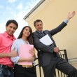 couple with their realtor in front of their new house — Stock Photo