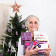 Old woman holding Christmas presents — Stock Photo