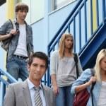 Three students walking down stairs alongside teacher — Stock Photo #8657395