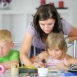 Stock Photo: Mother helping her kids with the homework