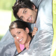 Stock Photo: Young couple peeking out of their tent