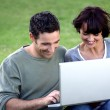 Couple sat with laptop in the park — Stock Photo