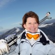 Stock Photo: Middle-aged woman skiing on mountain
