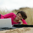 Woman using her laptop at the beach — Stock Photo