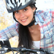 Young woman riding bike in the park — Stock Photo