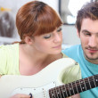 Man teaching a woman to play the guitar — Stock Photo