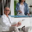 Young woman ironing and senior woman sitting on a sofa — Stock Photo