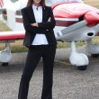 Young woman standing in front of an airplane - Stock Photo