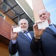 Two senior businessmen displaying their calling-cards — Stock Photo