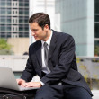Businessman sat using laptop in the city — Stock Photo