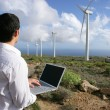 Man with laptop in wind farm - Stock Photo